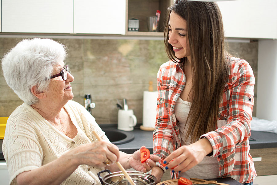 Girl helping elderly woman in kitchen