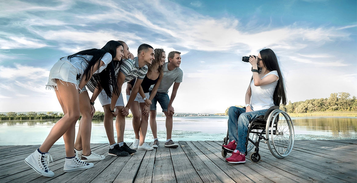 Disabled Female photographer shooting her friends under sunlight.